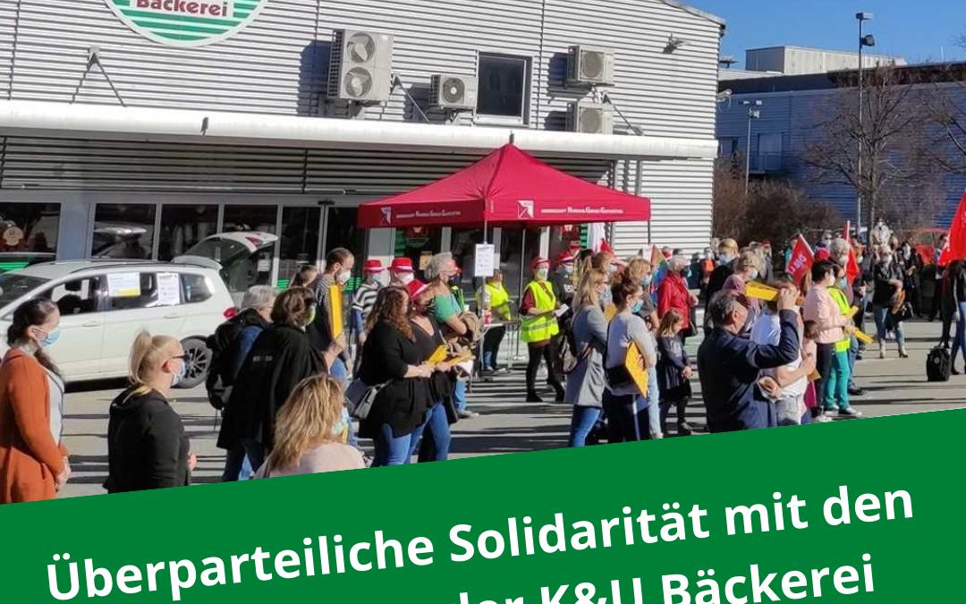 """Auf dem Bild zu sehen ist eine Demonstration an einer K&U Bäckerei. Über dem Bild liegt der Schriftzug """"Überparteiliche Solidarität mit den BEschäftigten der K&U Bäckerei"""""""