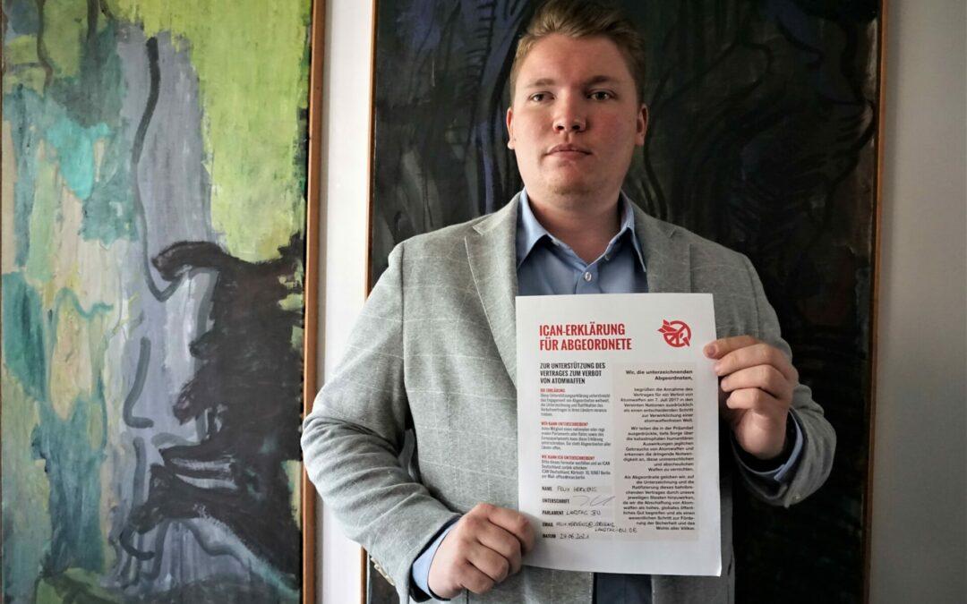 Auf dem Bild ist Felix Herkens zu sehen. In seiner Hand hält er die ICAN Erklärung zur Abschaffung von Atomwaffen.