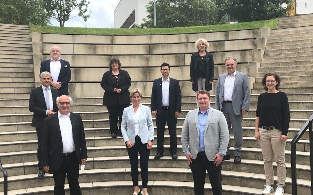 Auf dem Bild sind die Mitglieder des Wirtschaftsausschuss zu sehen, wie sie in einem Halbkreis auf einer Treppe stehen.