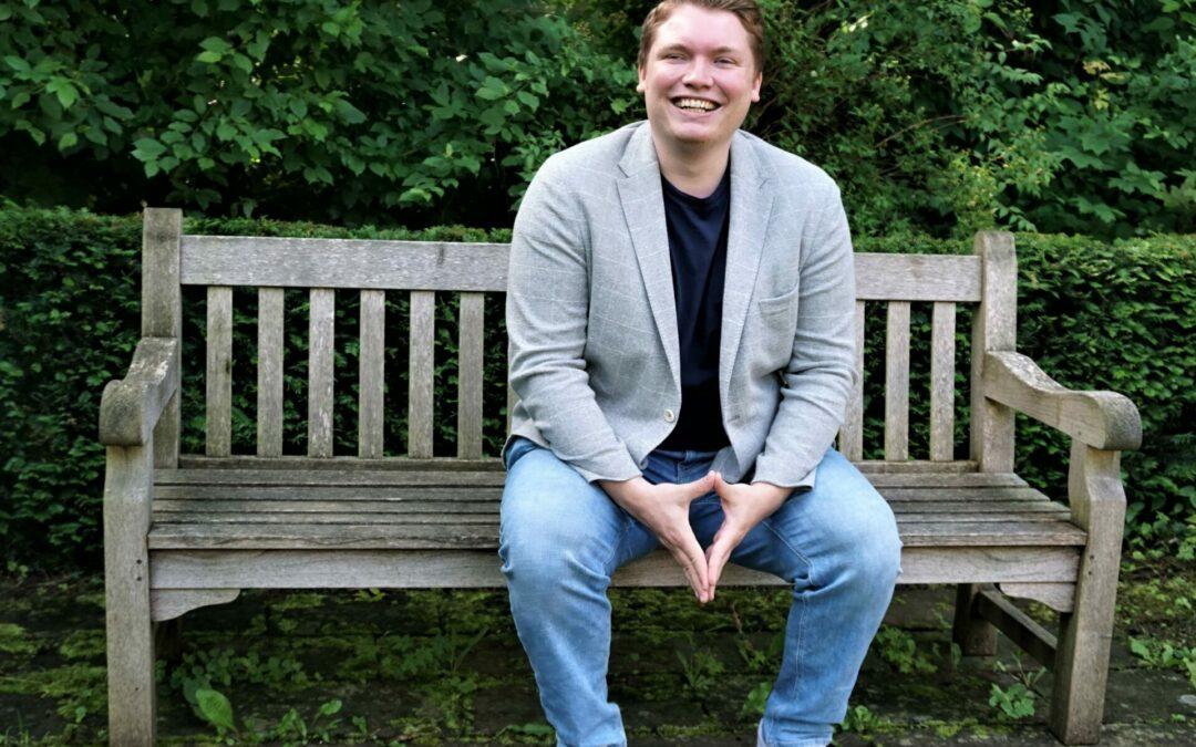 Felix Herkens sitzt auf einer Bank und lacht in die Kamera